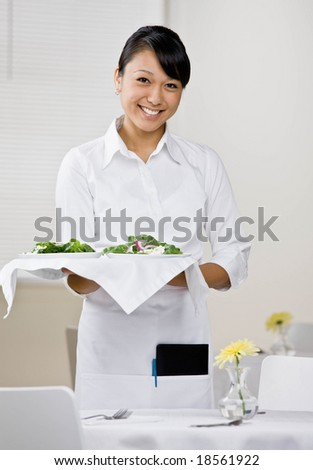 Happy waitress serving healthy salad for lunch in elegant restaurant