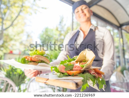 happy waitress with typical italian specialty. concept about jobs, food and service - stock photo