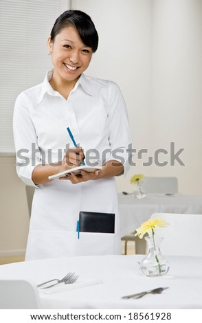 Happy waitress writing lunch order in elegant restaurant