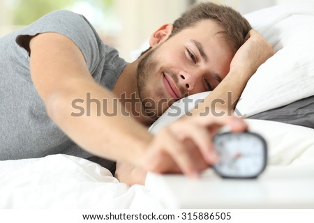 Happy wake up of a happy man lying on the bed and stopping alarm clock - stock photo