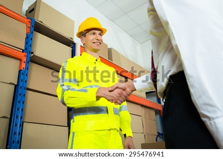 Happy Warehouse Worker In Reflective Clothing Shaking Hands With Manager