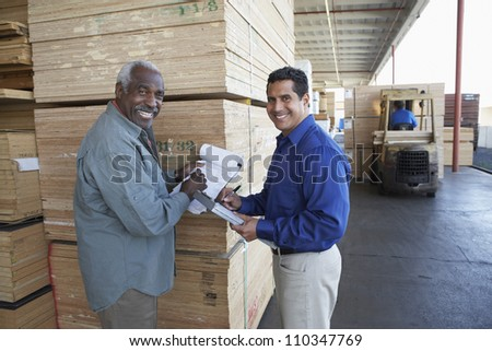 Happy warehouse workers holding clipboards