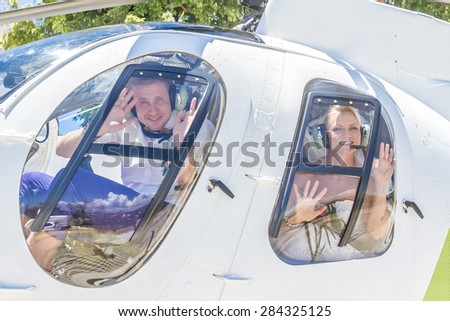 happy wedding couple bride and groom riding helicopter - stock photo