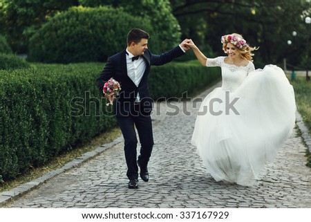 Happy wedding couple charming groom and blonde bride dancing in park - stock photo