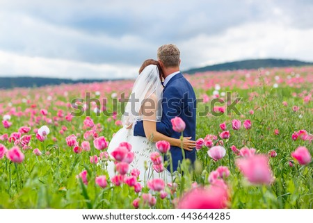 Happy wedding couple in pink poppy field. Beautiful bride in white dress and groom kissing and having fun in flower field on summer day. Just married, young family. - stock photo