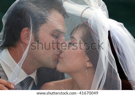 Happy wedding couple kissing under the bride's veil