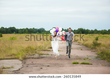 Happy wedding couple runs cheerful holding in hands colorful latex balloons. Beautiful bride and groom. Smiling and laughing people. Carefree woman and man. Decor for party. Freedom concept - stock photo