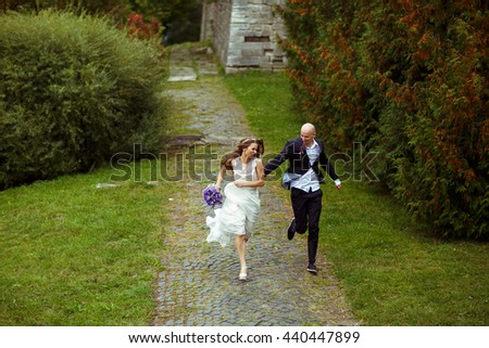 Happy wedding couple runs in the park