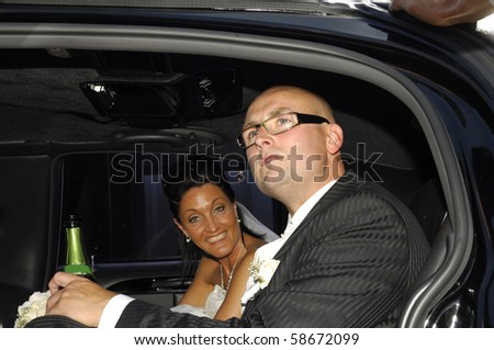 Happy wedding couple sitting in fine car. - stock photo