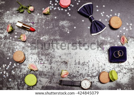 Happy wedding day concept. White gold luxury necklace, macaroones, two wedding rings on the velvet box, deep blue bowtie, roses, lipstick and men's watch on the table. Place for text. - stock photo
