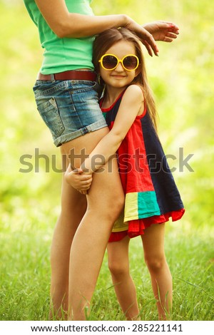 Happy weekend concept. Portrait of smiling gorgeous baby girl in trendy sunglasses hugging her mother. Family walking in the park. Stylish casual clothes. Sunny summer day. Outdoor shot