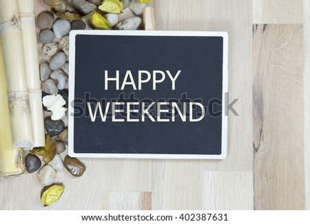 happy weekend on chalkboard with a bamboo and pebbles envelope notes against wooden background - office abstract. Retro design - stock photo