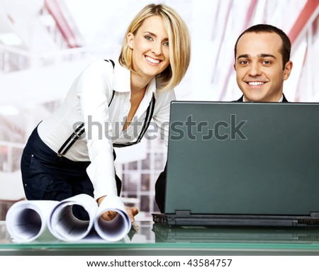 happy white collar workers over laptop and blueprints - stock photo