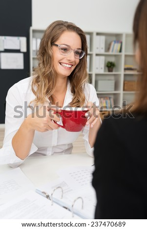 Happy White Office Girl Wearing Long Sleeve Shirt and Eyeglasses, Having Coffee Break with Co-worker at her Worktable. - stock photo