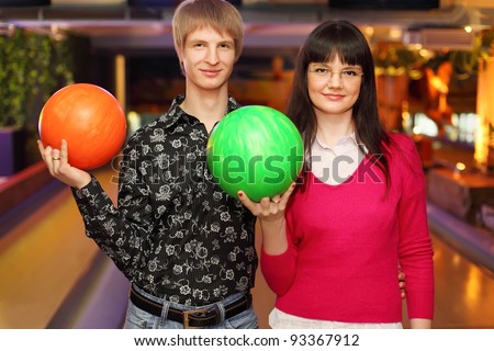 happy wife and husband with balls stand in bowling club and look at camera - stock photo