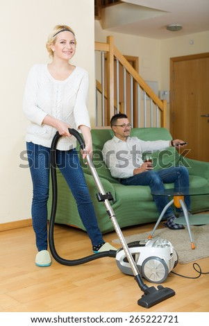Happy wife hoovering the room, her husband relaxing on a couch