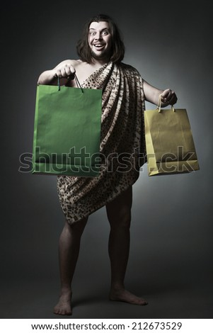 Happy wild man wearing skin of breast hold shopping bags. - stock photo