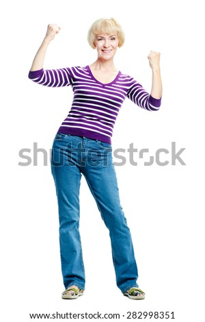 Happy winner. Happy elderly woman keeping arms raised and looking at camera while standing isolated on white background - stock photo