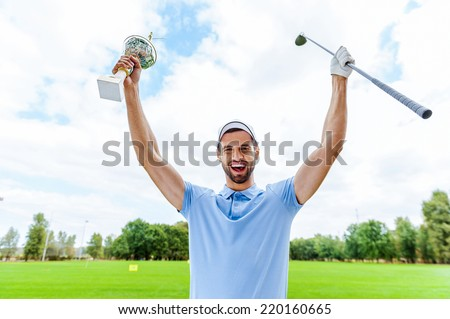 Happy winner. Happy male golfer holding trophy and driver while standing on golf course  - stock photo