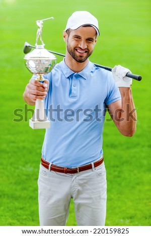 Happy winner. Happy male golfer showing his trophy and carrying driver on shoulder while standing on golf course  - stock photo