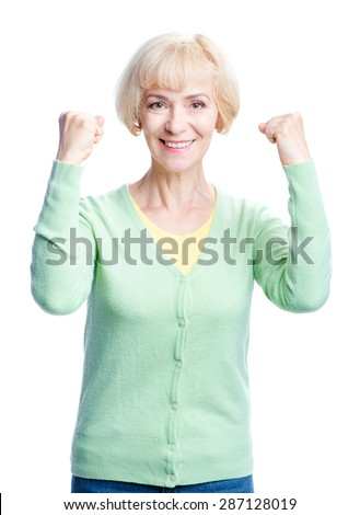Happy winner. Smiling elderly woman keeping arms raised and looking at camera while standing isolated on white background - stock photo