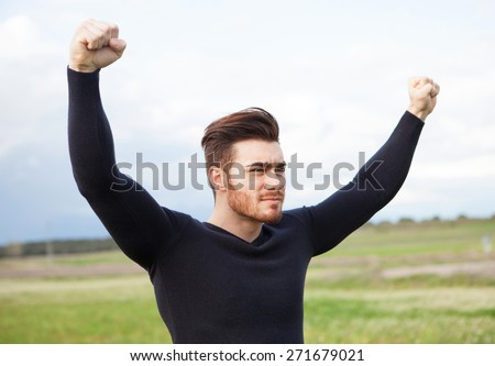 Happy winner strong man in the meadow  - stock photo