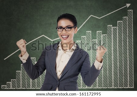 Happy winning business woman with arms up on growing graph background