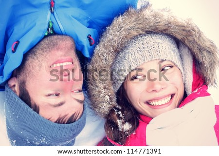 Happy winter couple. Cropped view of the faces of a joyful young interracial Asian / Caucasian couple lying on their backs in snow with their heads close together. - stock photo