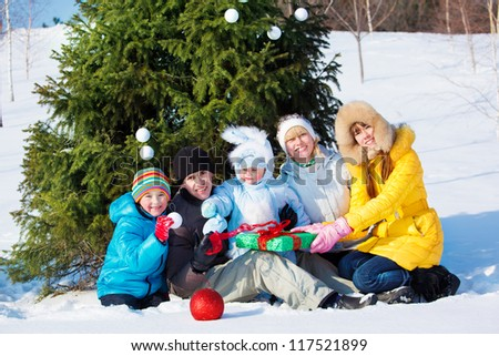 Happy winter family sitting beside Christmas tree - stock photo