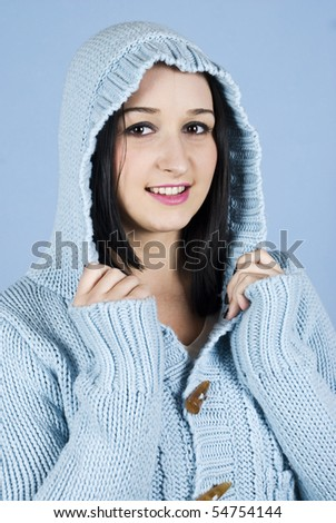 Happy winter girl in blue wool hood over blue background