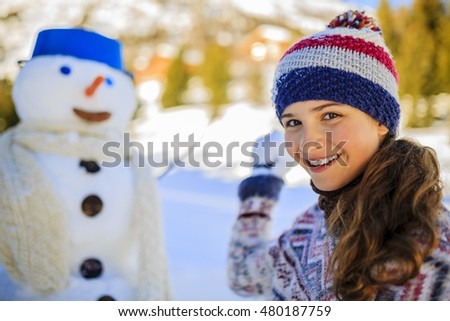 Happy winter girl wearing knitted wear scarf. Excited beautiful smiling teenager playing with snowman and snowball.