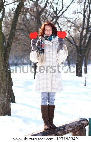 Happy winter girl with two red hearts standing on bench outdoors - stock photo