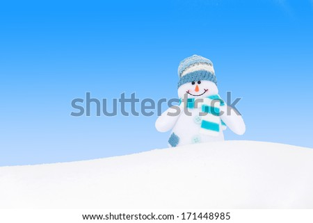 Happy winter snowman against blue sky background - stock photo