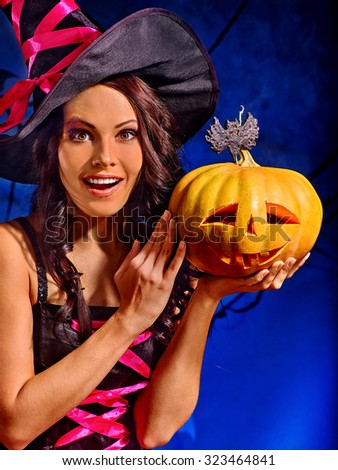 Happy witch holding orange carving pumpkin