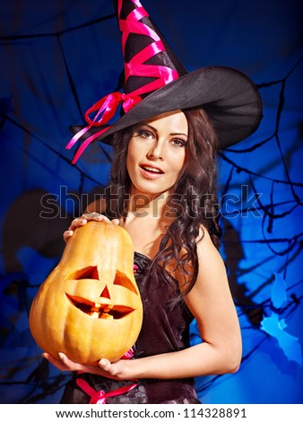 Happy witch holding pumpkin.