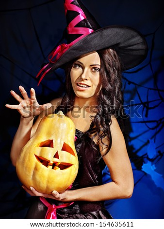 Happy witch holding pumpkin
