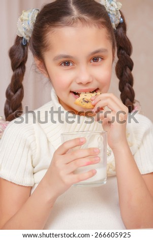 Happy with a dessert. Close-up of a small girl biting a piece of cookie and holding a glass of milk - stock photo