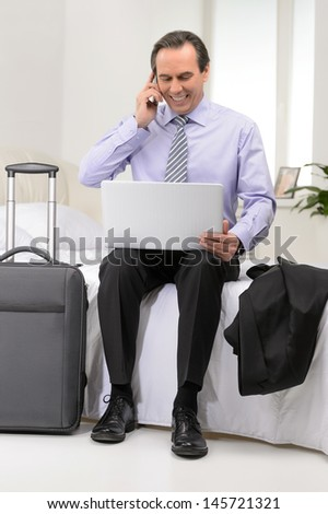 Happy with the results. Mature businessman sitting on the sofa at his hotel room - stock photo