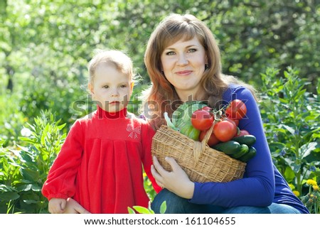 Happy woman and baby with vegetables harvest in garden - stock photo