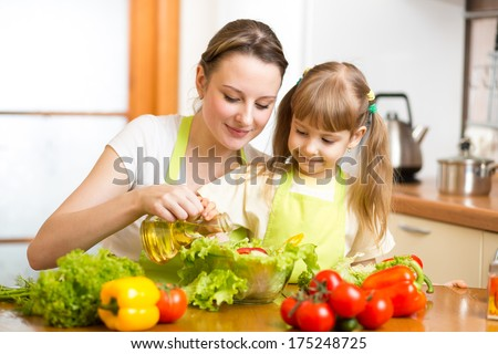 Happy woman and child cooking at kitchen - stock photo