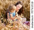 Happy woman and child eating bread in spring wheat field - stock photo