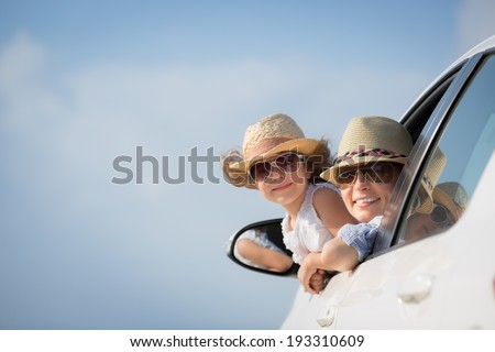 Happy woman and child in car against blue sky background. Summer vacation concept - stock photo