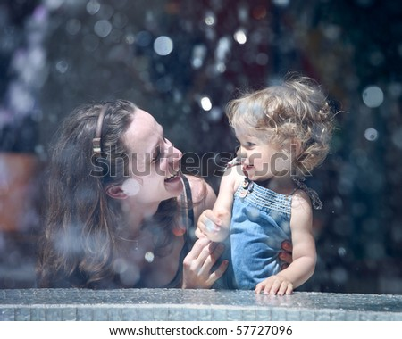 Happy woman and child in fountain splashes - stock photo