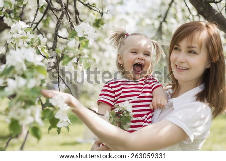 Happy woman and child laughing and playing in the park - stock photo