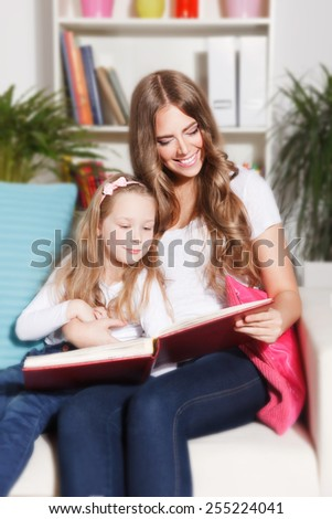 Happy woman and child reading a book - stock photo