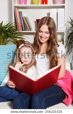 Happy woman and child reading a book