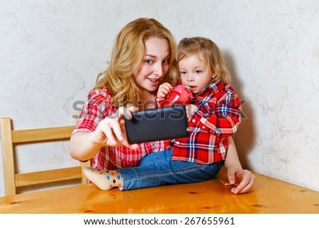 Happy woman and child taking a selfie. Sitting in the kitchen. Happy family. Mother holding a cell phone. Happy motherhood. - stock photo