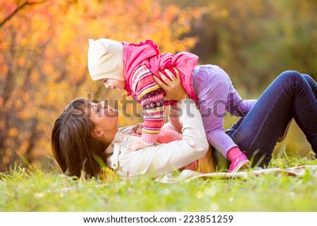 happy woman and daughter child play outdoors in fall - stock photo