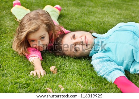 Happy woman and girl lie in autumn park - stock photo