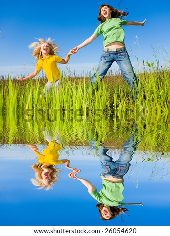 Happy woman and girl making exercises on field. - stock photo